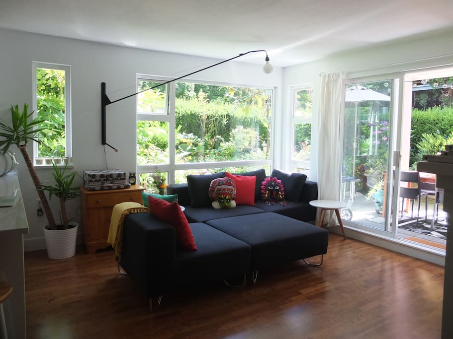 Bright, spacious, open-concept living room with fireplace and TV. This room faces on to private groundfloor patio and garden, as well as kitchen and dining room
