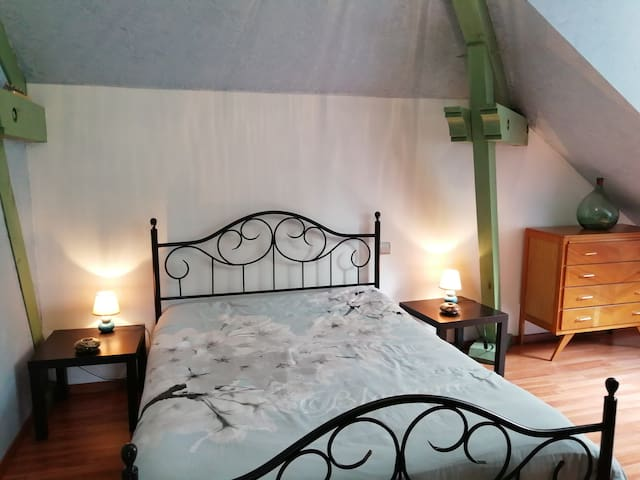 Une chambre avec un lit de 140 et un lit bébé.