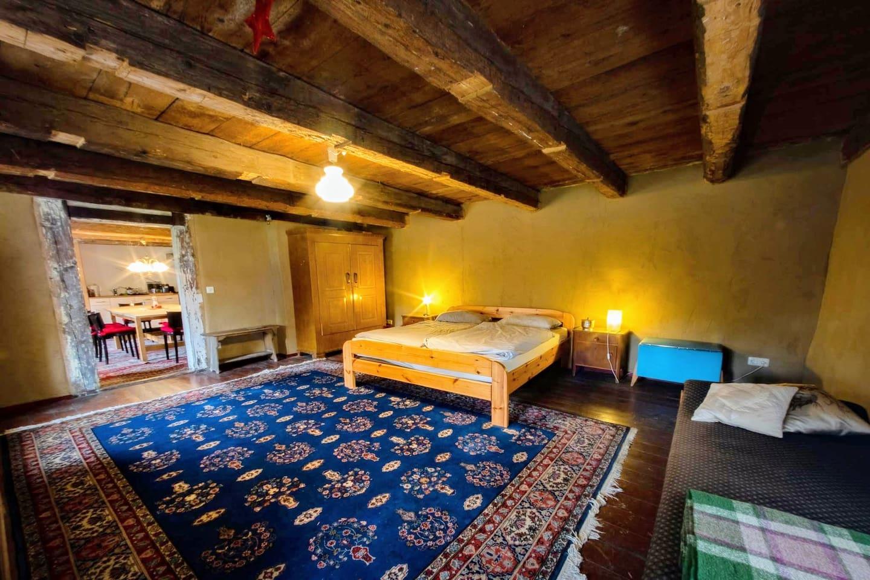 Der ungestrichene Lehmputz und die alten Deckenbalken schaffen in diesem Zimmer eine besondere Atmosphäre.  Und natürlich der blaue Teppich. Im Zimmer steht noch eine Liege und eine Truhe, auf der das Gepäck abgelegt werden kann.