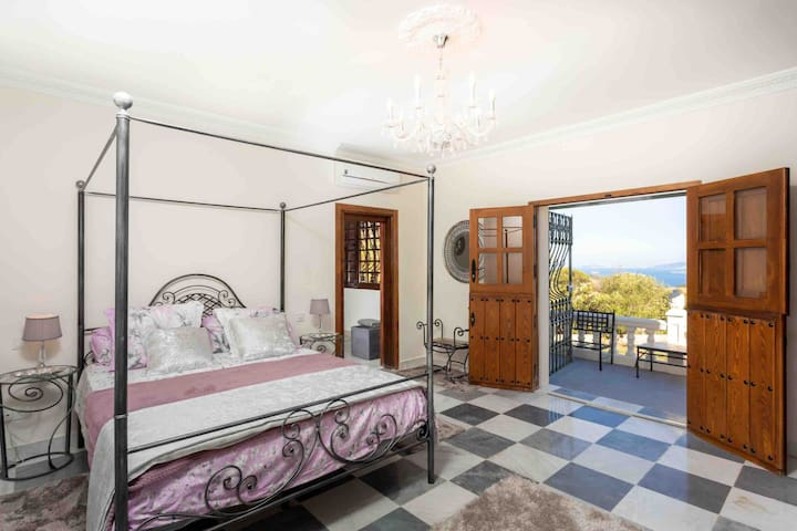 Beautiful master bedroom with marble tiles from an old convent. The bedroom has its own terrace with outdoor seating and wonderful views across to  Morocco.