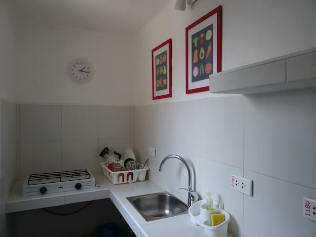 Petite cuisine équipée, réfrigérateur, vaisselle.