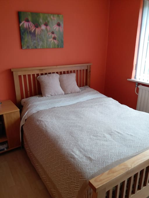 Double bed with memory foam mattress and wooden frame.