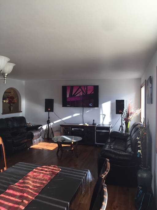 Living room with 70' TV and reclining sofa and love seats