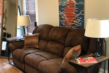 "The living room area features a 3 person couch with ends tables, a 55"" TV with a surround audio system. The TV is also supplied with an Amazon Fire Stick and Apple TV."