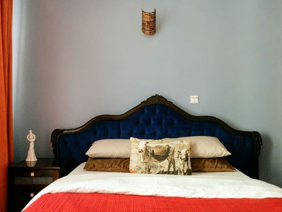 The bed is an antique with a comfortable queen sized. mattress
