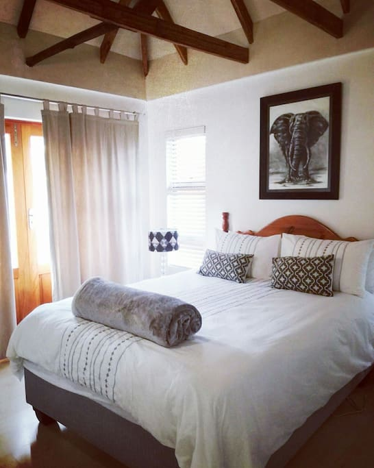 Come see the Main Bedroom with high beamed ceilings, hotel quality cotton sheets and covers and an en-suite bathroom. Enjoy the natural sunlight and feel free to open up double doors leading onto the outdoor entrance area