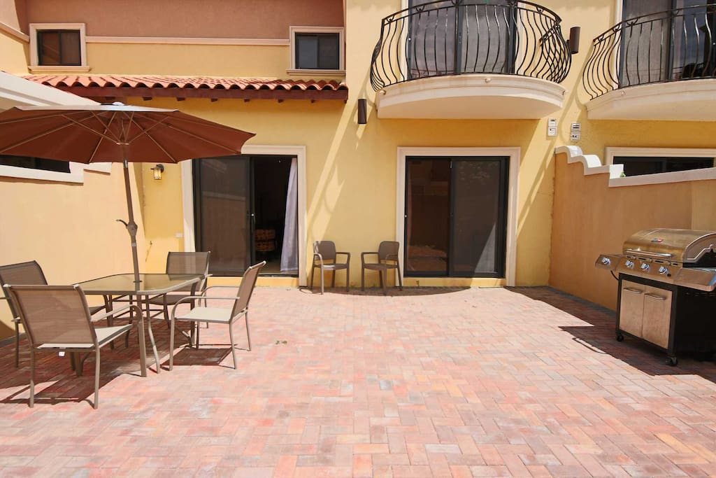 Patio with 4-seat dining table and BBQ-grill.