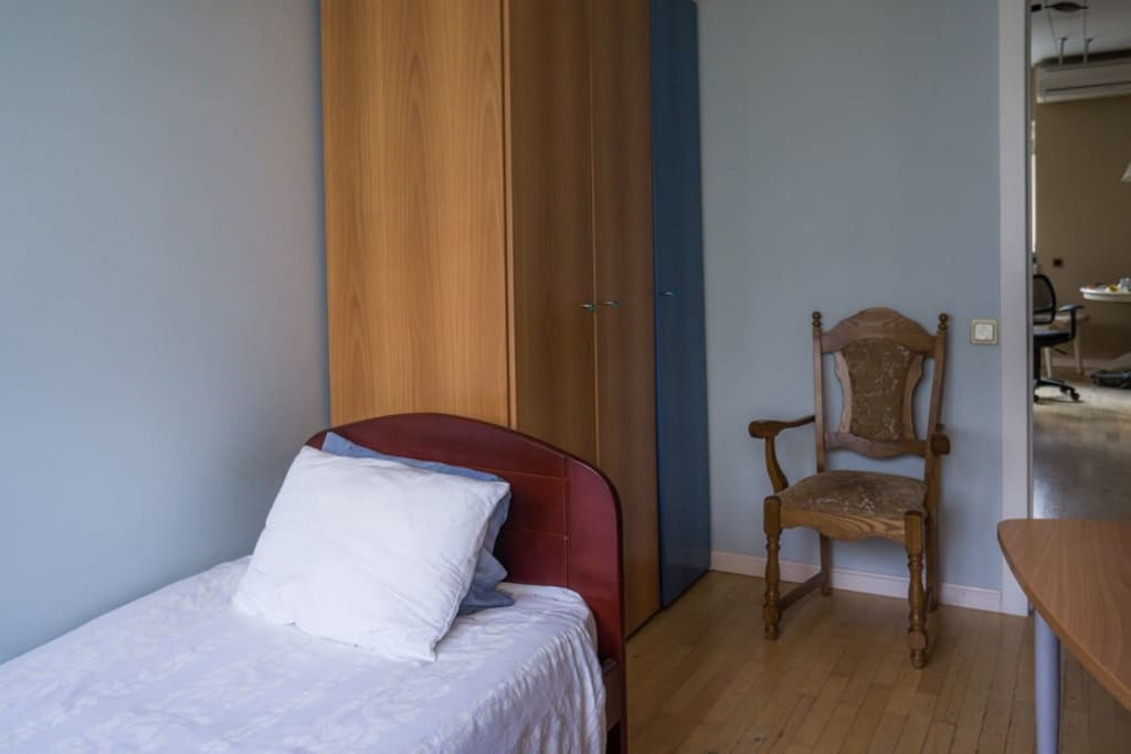 the view of the room — there is a cupboard, a table suitable for working and the bed