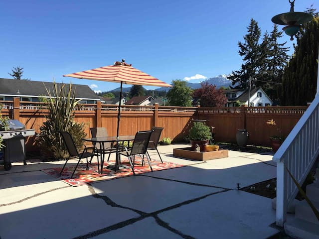Patio with privacy fence right outside the door and kitchen. Grill, table and chairs. A great place to hang out!