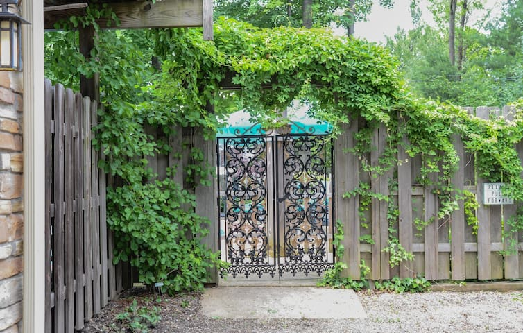 Black wrought iron gate entrance. End of driveway. Park next to gate.