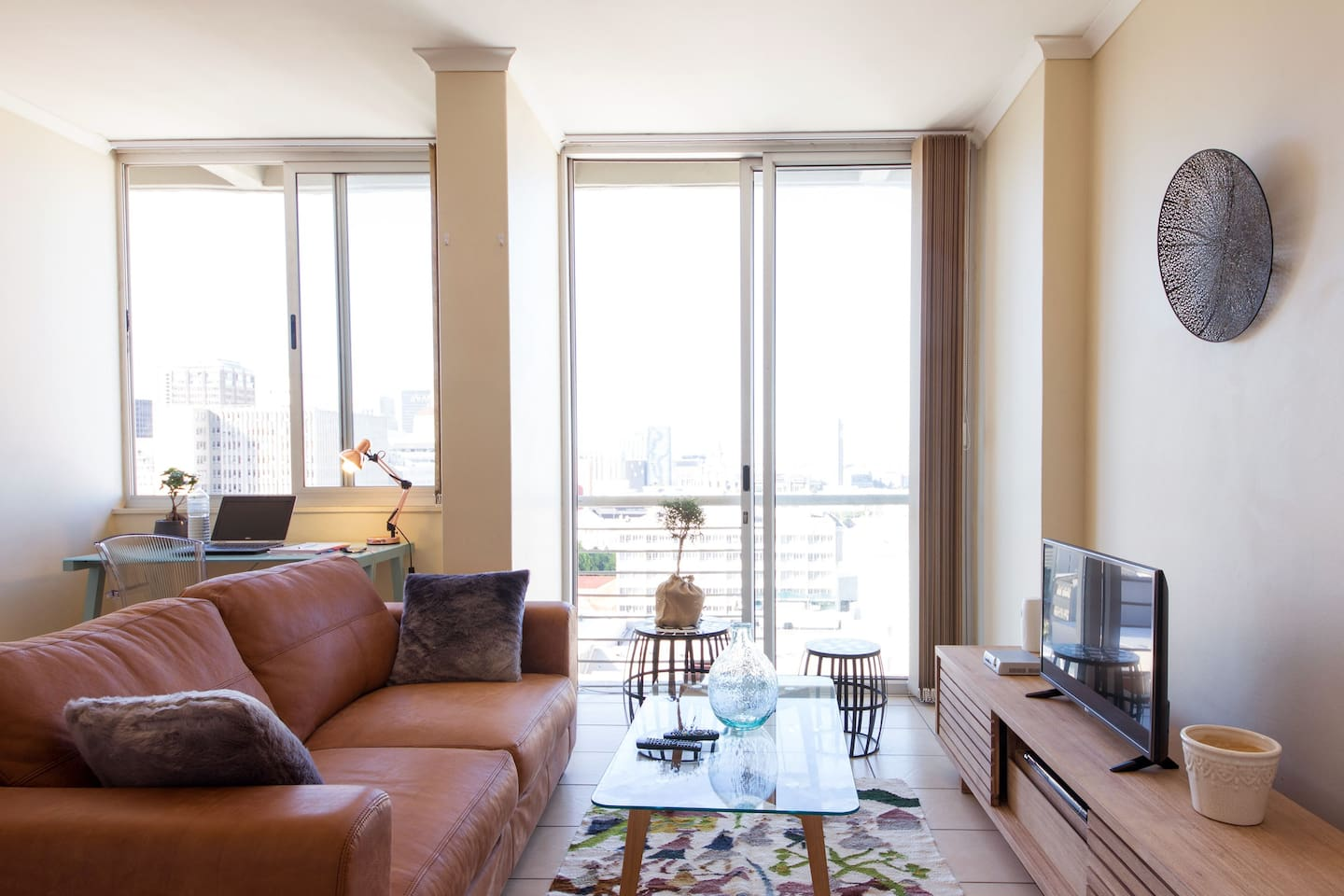 Comfortable lounge including a lovely leather couch with beautiful views of the Mother city day and night.