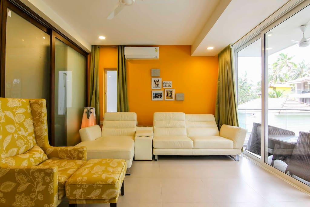 State of-art Living Room with leather sofa & built in sound system & upholstered chair with pouff.