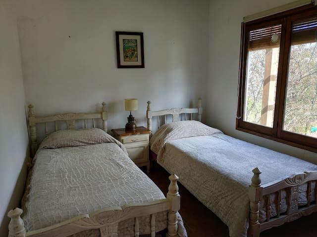Dormitorio 3 con dos camas de una plaza, con vista al jardin.Tejido mosquitero en la ventana.