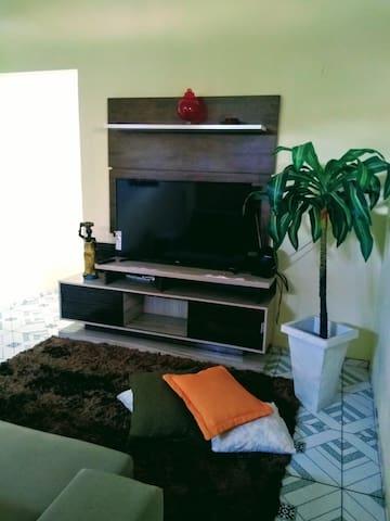 Sala com sofá, televisão e bem arejada