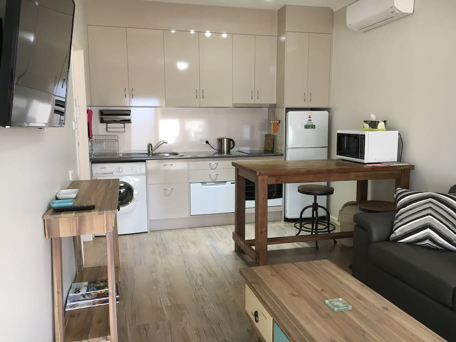 Modern kitchen dinette with sofa bed. Includes oven & induction plates, microwave & dishwasher, also washing machine.