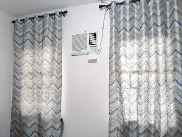 The aircon and two windows with dark curtains.