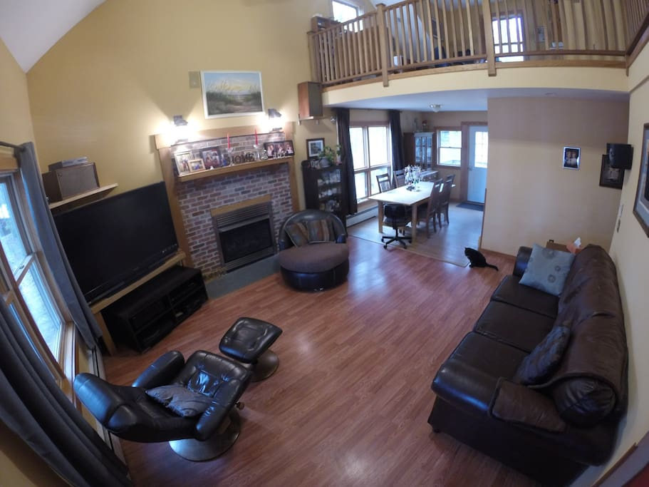 Living room with large screen TV and gas fireplace.