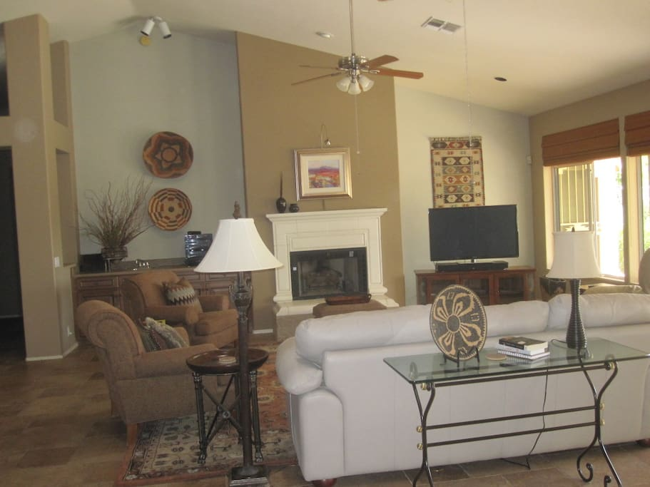 "Spacious comfy living room with 65""smart TV, fireplace, views of pool. patio, golf"