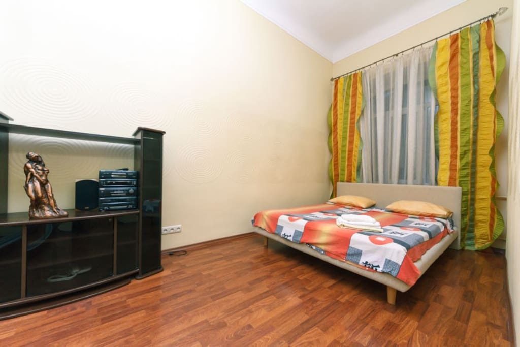 A bedroom with a double bed, a large curbstone, a music center and a window with access to Sofievskaya street