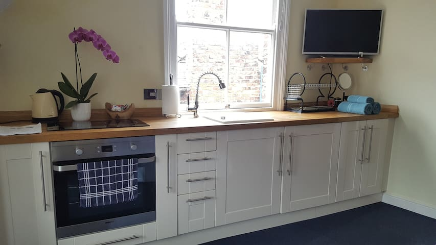"""Kitchen area with hob, oven, sink, kettle and fridge. 32"""" TV with Netflix. Light and airy room."""
