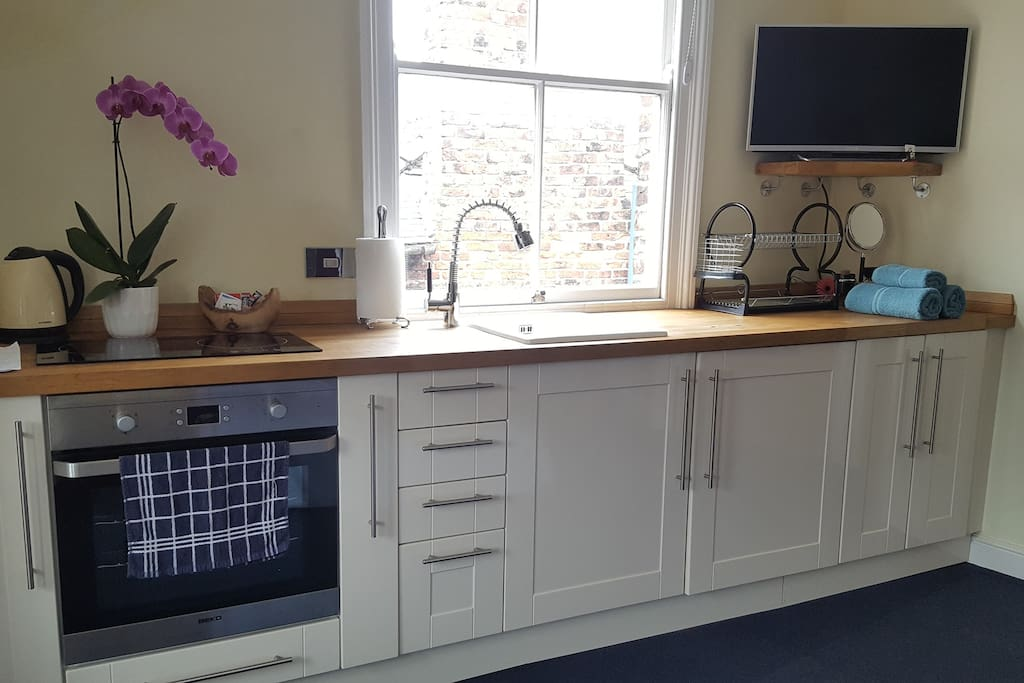 "Kitchen area with hob, oven, sink, kettle and fridge. 32"" TV with Netflix. Light and airy room."