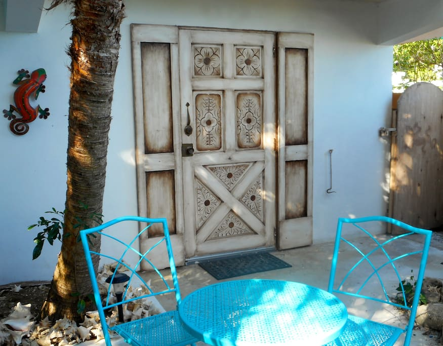 The entrance to the unit is an antique hand carved  wood door and there's a bistro table to relax over a cup of coffee or a glass of wine.