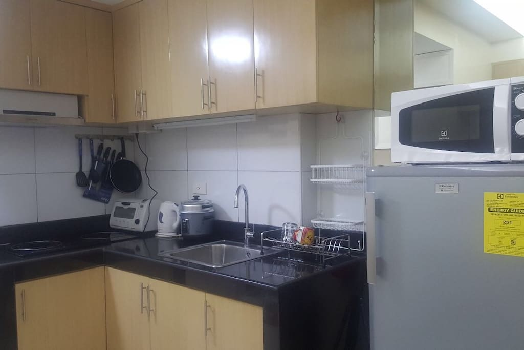 Big kitchen place with ref, microwave, oven toaster, kitchen utensils, kettle