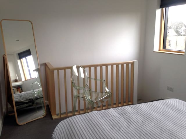Other side of bedroom, looking to stairs - door is at the bottom of stairs.