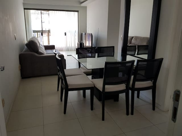 Entrada do Apto sala conjugada com mesa de vidro bom tamanho com 6 cadeiras decorada com espelho grande.