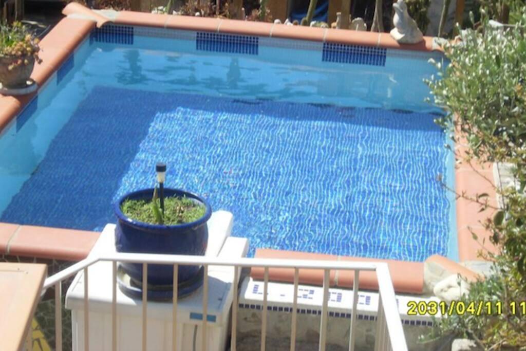 Une piscine en plein soleil en pierre, agréable et rafraichissante