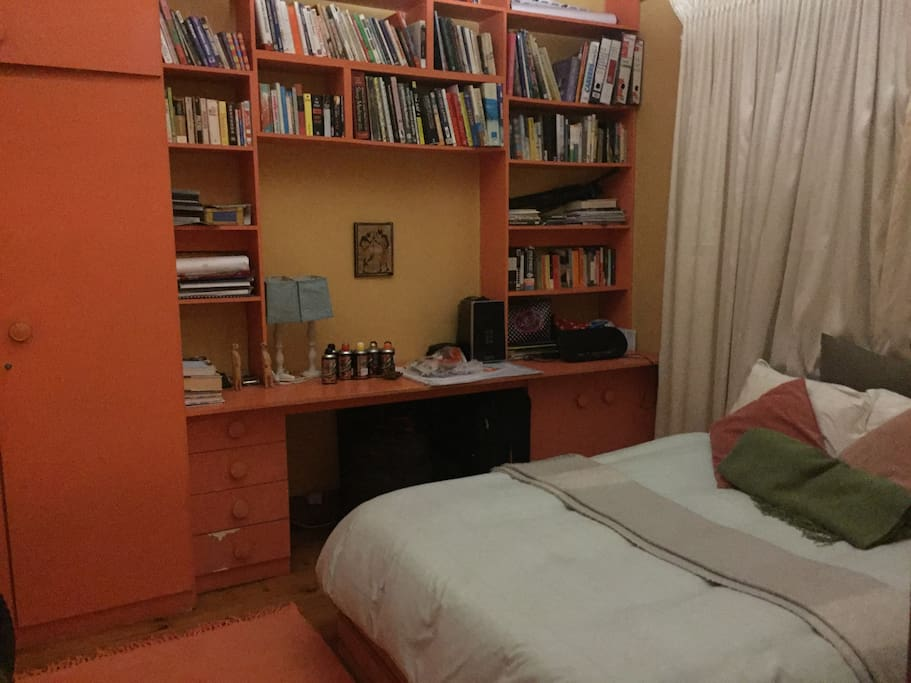 The warm and colourful guest room with double bed and cupboard space