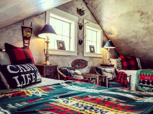 Sleeping loft equipped with 2 queen beds appointed in fine Pendleton blankets with sitting area.