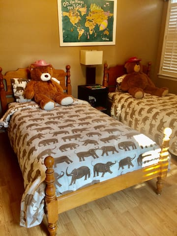 Twin bed room with toys and books for the kids.