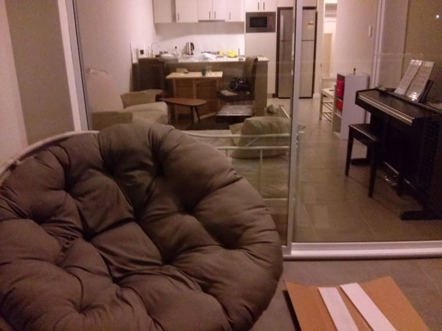 balcony with plush seating, perfect for reading. view into living room/dining area and kitchen. kitchen has a peninsula, brand new appliances including dish washer