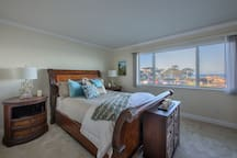 Master bedroom has a plush queen bed with luxurious linens.