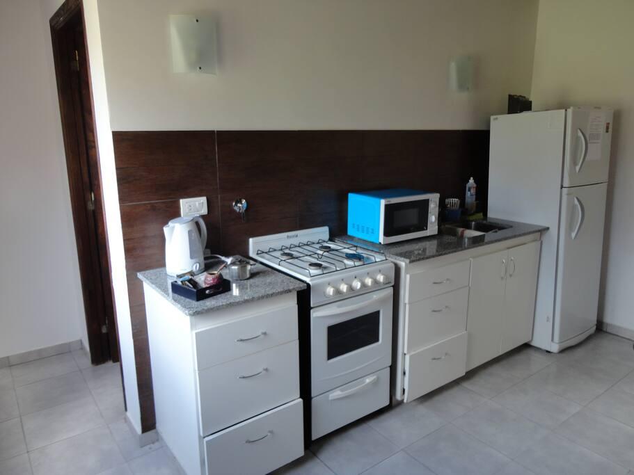 Cocina con vajilla completa. Heladera con freezer, microondas, pava eléctrica.