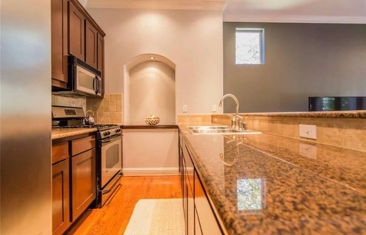 Kitchen with all the amenities! Large counter space and bar area, fridge, freezer, dishwasher, oven, microwave, coffee pot, tea kettle, etc.