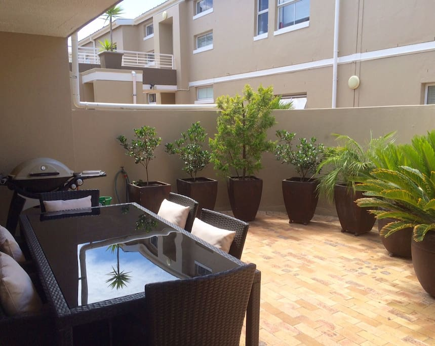 Private outdoor patio with gas barbecue and outdoor furniture