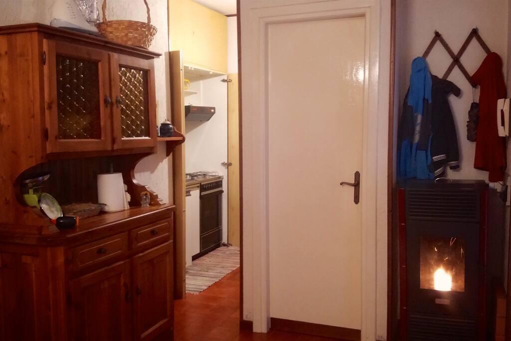 Sulla sinistra la zona cucina e la porta del bagno.