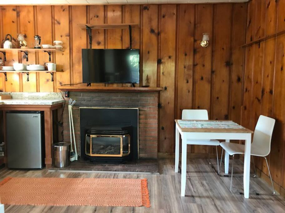 Wood planked cabin feel with fireplace and small dining table