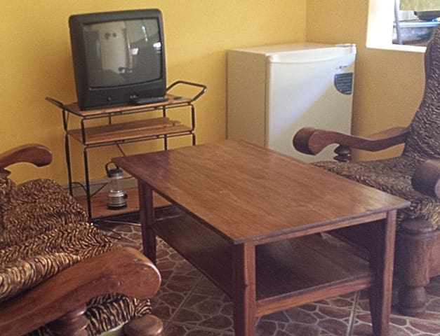 Sitting room with TV, fridge, small sofas etc. Among the advantages of staying in a private apartment compared to a guesthouse at similar rate in town.