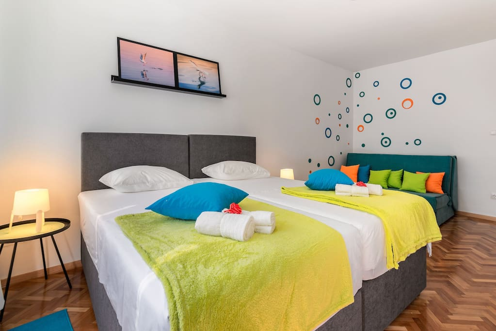 This is a big room. There are two boxspring beds that can be connected or separated if needed. The size of each bed is 90 cm × 200cm and when connected 180cm × 200cm. The room also has a sofa that extends into a bed 160cm × 200cm. The room is really big and is ideal for a couple with two or even three children and four friends.