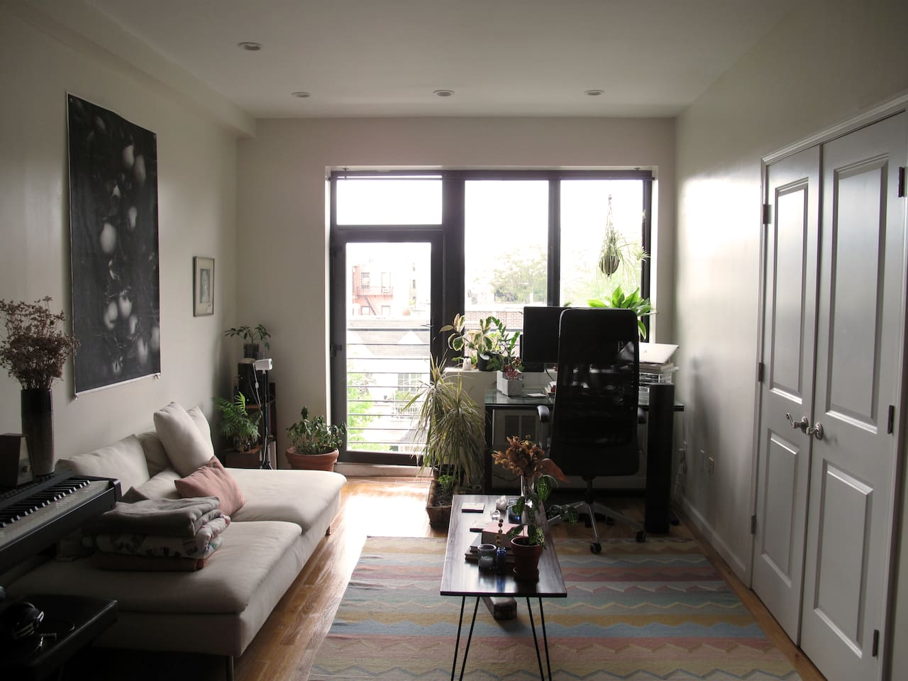 Living room with lots of sun, plants, balcony, a big couch, desk, & coffee table