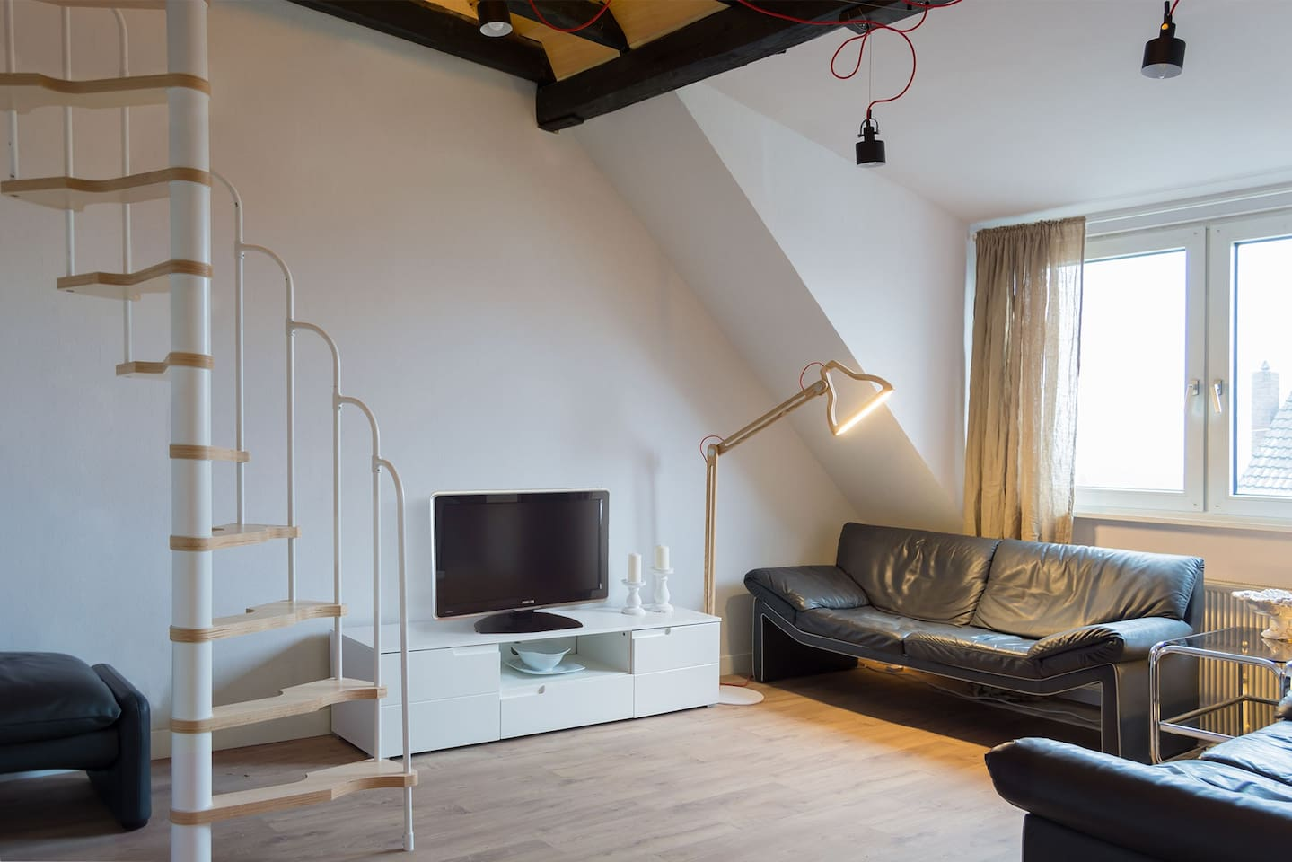 Spacious living room with a staircase to a small additional bedroom on the mezzanine.