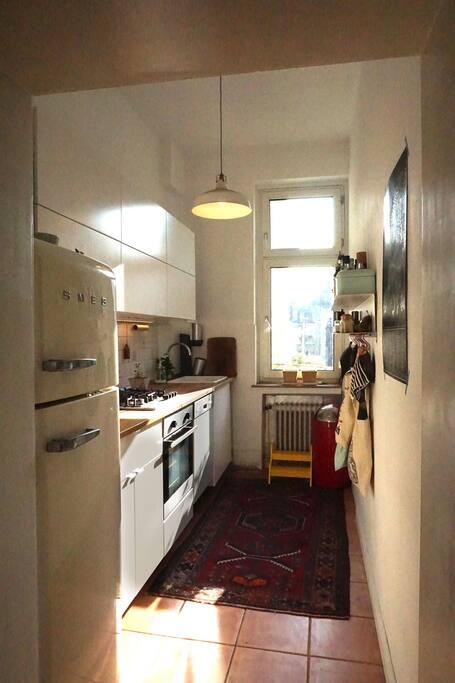 Küche mit Backofen, Gasherd, Spülmaschine und großem Kühlschrank