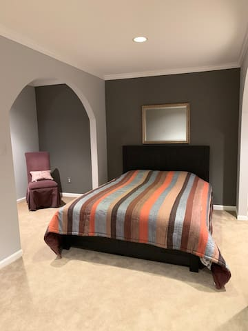 Queen sized bed with mini living room area next to it