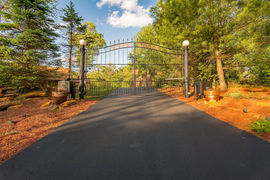 Blacktop driveway with a custom Iron Gate requiring code access.