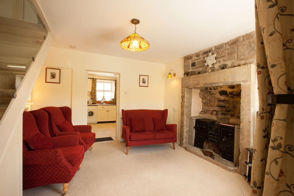 Cosy sitting room  with traditional hearth and range with visual coal-effect.