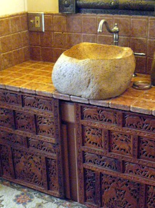 Your bathroom sink natural stone on carved wooden counter