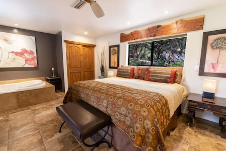 The bedroom area has a king bed with a window behind looking out onto the garden and panoramic red rock views straight ahead, through the living room windows.